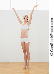 Gleeful fit woman in sportswear stretching raising her arms