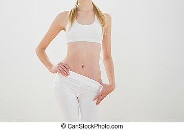 Slender blonde woman posing wearing sportswear with hand on...