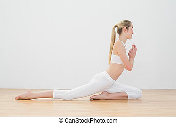 Calm ponytailed woman doing yoga pose sitting on floor