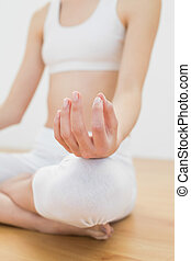Close up of slender young woman meditating sitting in lotus...