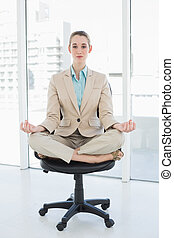Focused chic businesswoman sitting in lotus position on her...