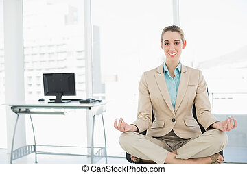Beautiful calm woman sitting in lotus position on her swivel...