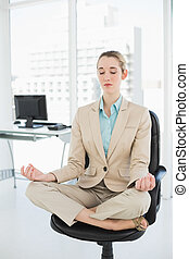 Lovely classy businesswoman meditating in lotus position on...