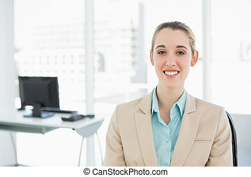 Happy classy woman sitting smiling on her swivel chair