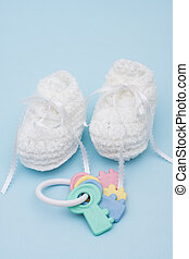 Baby Booties - Baby booties and rattle sitting on a blue...