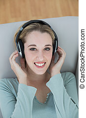 Gorgeous young woman listening with headphones to music smiling at camera lying on couch
