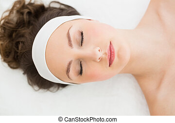 Brunette with eyes closed in beauty salon - Young brunette...