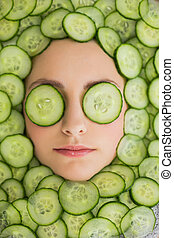 Beautiful woman with facial mask of cucumber slices on face...
