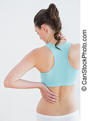 Rear view of a toned woman with back pain against wall -...
