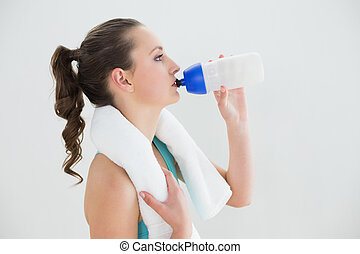 Side view of fit woman drinking water at the gym