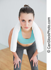Tired woman with towel around neck at fitness studio -...
