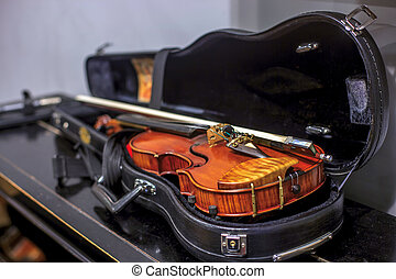 Violin in a case, lies on the piano