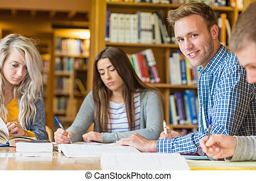 Smiling male student with friends at library desk - Portrait...