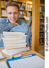 Portrait of a smiling male student with stack of books while...