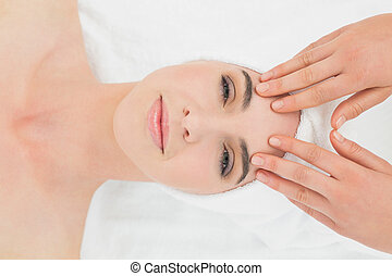 Hands massaging woman's forehead at beauty spa