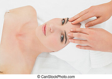 Hands massaging womans forehead at beauty spa - Close up of...