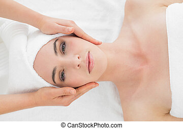 Hands massaging womans face at beauty spa - Close up of...