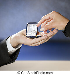 marriage proposal - close up of young couple getting engaged...