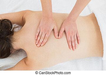 Woman enjoying back massage at beauty spa