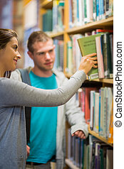 Two young students selecting a book in the library - Blurred...