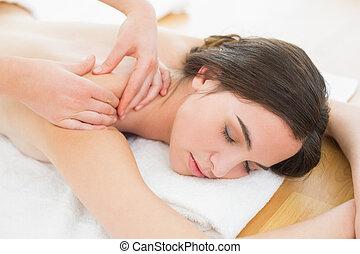 Beautiful woman enjoying shoulder massage at beauty spa -...