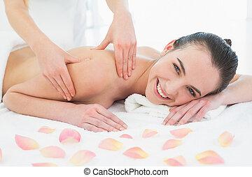 Woman enjoying shoulder massage at beauty spa - Close up of...