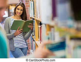 Student reading a book by bookshelf in the library -...