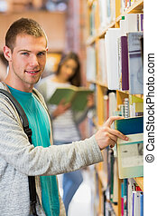 Student selecting a book from bookshelf in the library -...