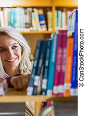 Smiling female student selecting book in the library - Close...