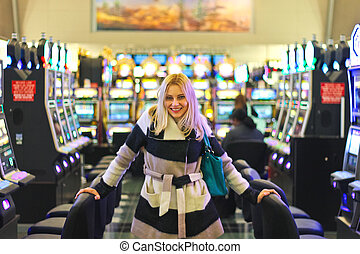 Happy girl near the slot machines at the airport in Las...