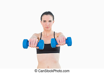 Portrait of a serious young woman with dumbbells against...