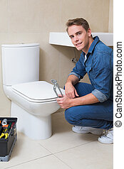 Handsome plumber with toolbox doing toilet reparation -...