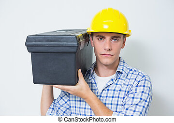 Serious handyman in yellow hard hat carrying toolbox -...