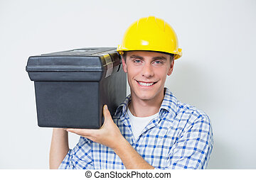 Smiling handyman in yellow hard hat carrying toolbox -...