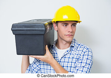 Serious handyman in yellow hard hat carrying toolbox against...