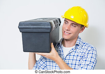 Smiling handyman in yellow hard hat carrying toolbox against...