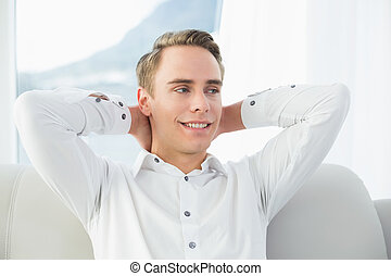 Smiling relaxed young man sitting on sofa in a bright house