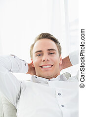 Smiling relaxed young man lying on sofa - Portrait of a...
