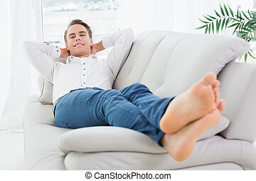 Full length of a relaxed young man lying on sofa in a bright...