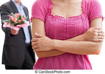 Angry woman and a man with bouquet of flowers in the...