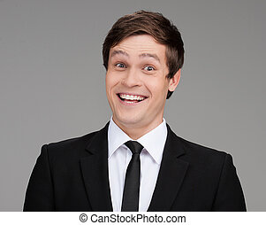 Happy businessman. Portrait of cheerful young businessman looking at camera and smiling while isolated on grey