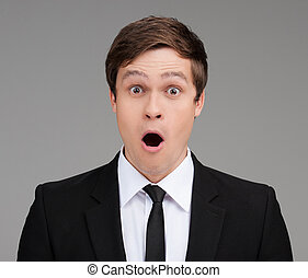 Shocked businessman. Portrait of surprised young businessman...