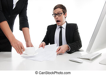 What are you doing? Stressed young businessman shouting at his secretary putting a cup of coffee on the documents