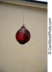 Red ball - A red ball is hanging from a string.