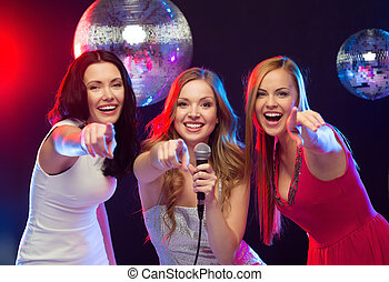 three smiling women dancing and singing karaoke - party,...