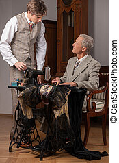 Tailors at work. Two confident tailors working at the tailor...