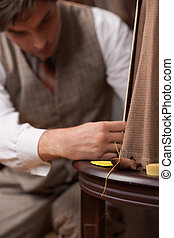 Tailor at work. Confident young tailor sewing clothes at...