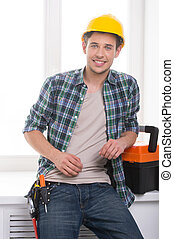 Handyman. Cheerful craftsperson looking at camera and...