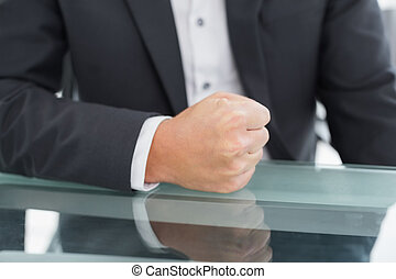 Mid section of businessman with clenched fist on office desk...