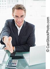 Elegant businessman offering a handshake at office desk -...
